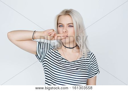 Beautiful blonde teenage girl posing, making a kissy face, standing against white wall. Two fingers gesture