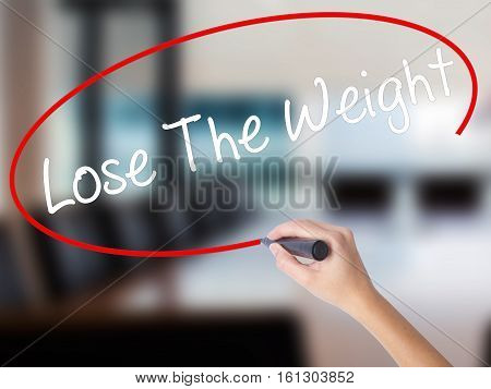Woman Hand Writing Lose The Weight With A Marker Over Transparent Board