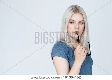 Young woman with straight blond dyed hair looking to the side and thinking on white background. Thoughtful girl