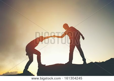 Friend Hiking Help Each Other Silhouette In Mountains
