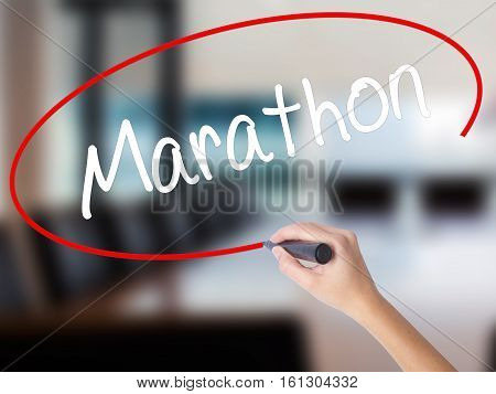Woman Hand Writing Marathon With A Marker Over Transparent Board.