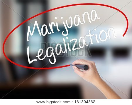 Woman Hand Writing Marijuana Legalization With A Marker Over Transparent Board