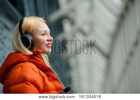 Girl in orange jacket listening music on headphones indoors