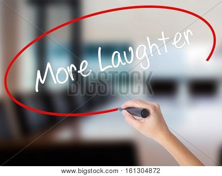 Woman Hand Writing More Laughter With A Marker Over Transparent Board