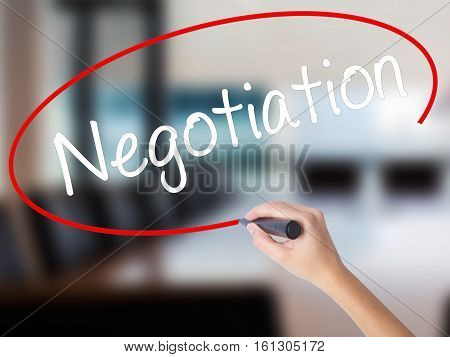 Woman Hand Writing Negotiation  With A Marker Over Transparent Board.