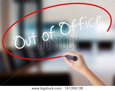 Woman Hand Writing Out Of Office With A Marker Over Transparent Board