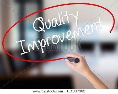 Woman Hand Writing Quality Improvement With A Marker Over Transparent Board.