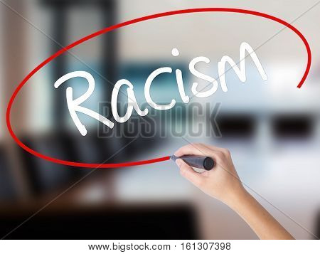 Woman Hand Writing Racism With A Marker Over Transparent Board.