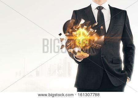 Debt concept. Businessman holding exploding wrecking ball with golden dollar sign inside on light city background