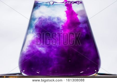 Early color change in chemical chameleon reaction. Intense pink of potassium permanganate solution turns purple when poured into sucrose and sodium hydroxide in water