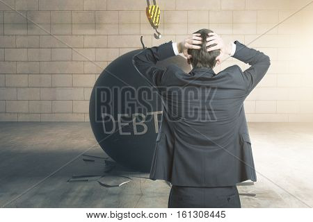 Debt concept. Stressed businessman with wrecking ball