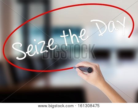 Woman Hand Writing Seize The Day With A Marker Over Transparent Board.