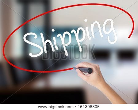 Woman Hand Writing Shipping With A Marker Over Transparent Board.