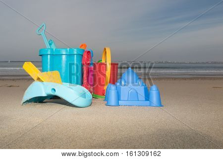 lot of plastic toys in sand beach waiting kids playing