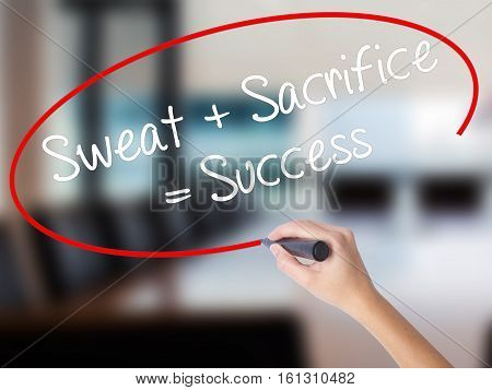 Woman Hand Writing Sweat + Sacrifice = Success With A Marker Over Transparent Board