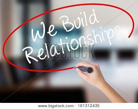 Woman Hand Writing We Build Relationships With A Marker Over Transparent Board