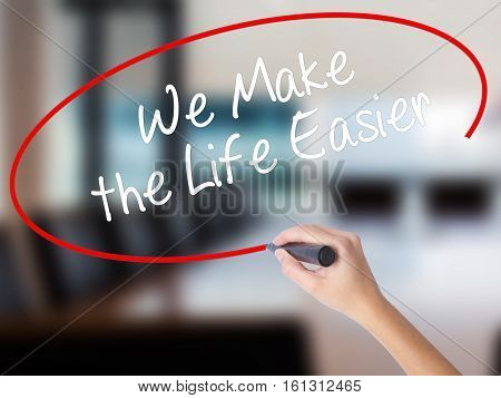 Woman Hand Writing We Make The Life Easier With A Marker Over Transparent Board