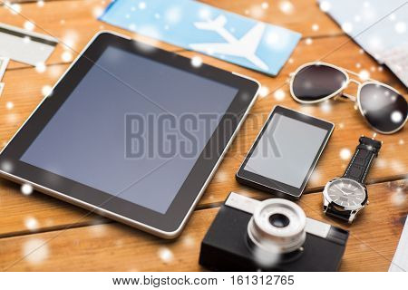 travel, tourism, technology and winter holidays concept - smartphone with tablet pc computer, airplane ticket and personal stuff over snow