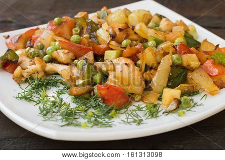 Saute vegetables and roasted chicken. Wooden table. Rural background
