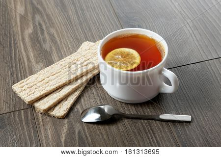 white cup of tea with lemon teaspoon and cookies on a wooden table
