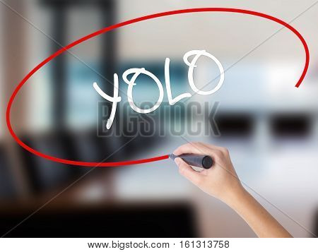 Woman Hand Writing Yolo (you Only Live Once) With A Marker Over Transparent Board