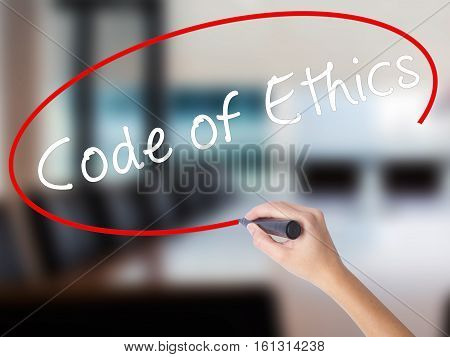 Woman Hand Writing Code Of Ethics With A Marker Over Transparent Board