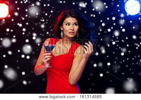 people, winter holidays, party, alcohol and leisure concept - beautiful sexy woman in red dress with cocktail glass at nightclub over snow