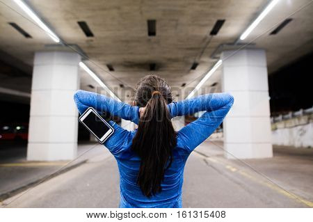 Beautiful young runner under the bridge in the town in the evening with smart phone, using a fitness app for tracking weight loss progress, running goal or summary of her run. Warming up and stretching. Rear view.