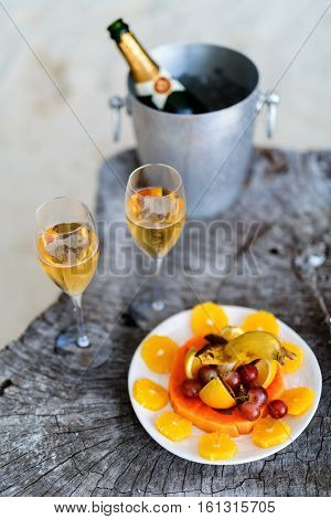 Two glasses with champagne  and fruits on wooden vintage tray served for special occasion or celebration
