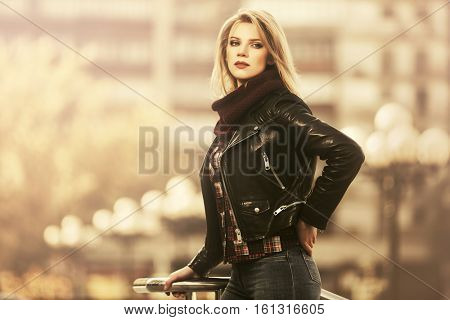 Young blond woman in leather jacket walking on city street. Stylish fashion model outdoor