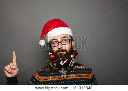 Geeky young man with glasses wearing santa claus hat with funny christmas decorated beard pointing upwards with his finger over grey background