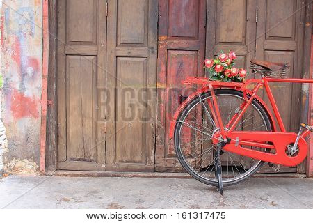 flower on saddle red bicycle classic vintage on wall wood background with copy space for add text