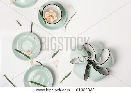 Clean dishes, coffee or tea set. Composition of elegant porcelain cups and saucers with flower petals and copy space at white background, high key, top view and flat lay.