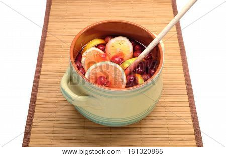 Nonalcoholic drink from cranberries and lemon in big round green pot with wooden spoon inside indoor on brown straw mat isolated on white front view