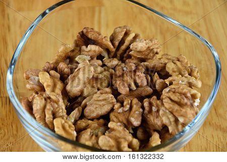 Walnuts in a glass bowl. Walnuts. Wood backgroung.