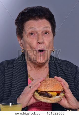 Funny grandmother eating burger portrait.