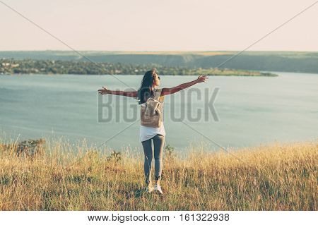 Hipster Travel girl with backpack and outspread hands. Toned colors. Film effect