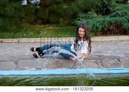 beautiful woman sitting near the fountain in the Park.