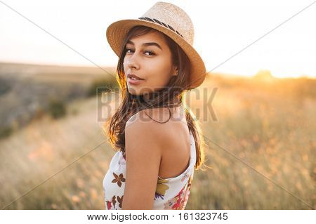Fashion portrait of latin trendy young woman with stylish hat. Spanish female in meadow over sunrise
