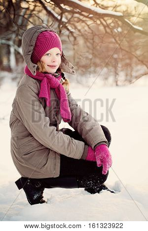 Happy Child Girl in Winter Jacket and Pink Woolen Hat and Scarf in Winter Park Outdoors