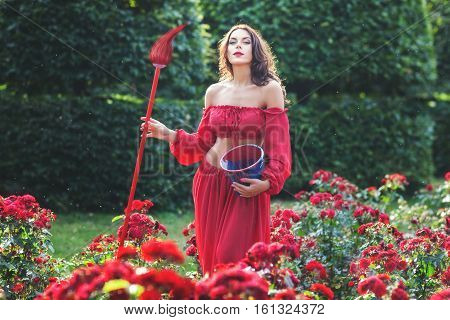 Woman holding a brush she paints flowers in the garden.