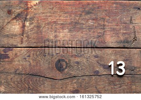 Inscription Thirteen made from digits on old wooden background