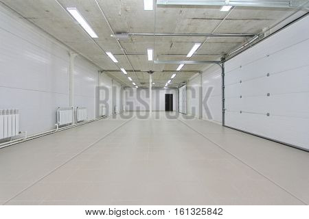 empty light parking garage warehouse interior with large white gates and gray tile floor