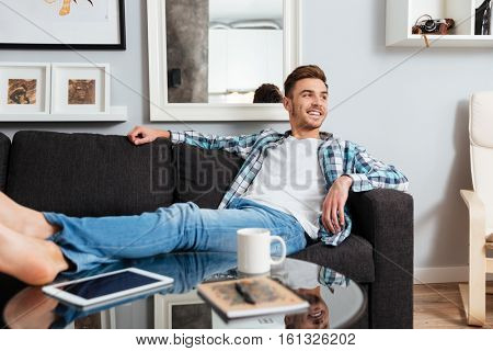 Picture of happy bristle man dressed in shirt in a cage print lies on sofa in home and looking aside.