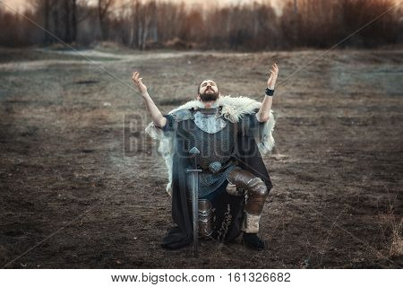 Man in the iron armor of a warrior raised his hands to the sky.