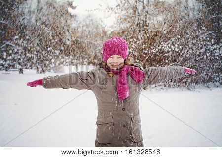 Cute Child with red hat in Snowy Winter Outdoors