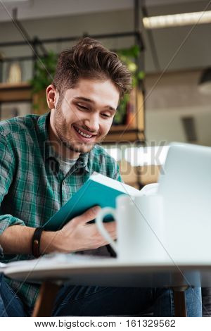 Vertical image of handsome man in green shirt sitting by the table and reading book in office. From below photo. Coworking