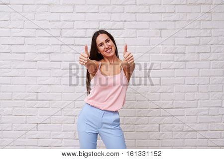 Mid shot of exhilarating woman posing with two thumbs up. Looking at the camera. Beautiful longhaired woman wearing nice well-combined suite
