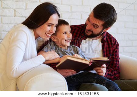 Close-up of tight-knight family. Spending time together. Parents supporting a child while reading, positive achievements of а kid