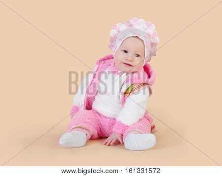 Little baby girl sitting. Beige background, isolated